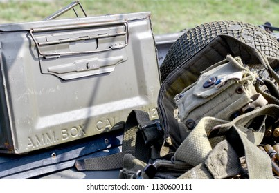 an ammo belt, metal ammo box and helmet rest alongside a military tool belt. All ready for an american soldier