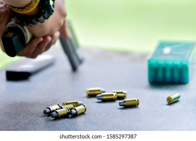 The ammunition box is placed on the table during the firing range and the man is about to fire the gun.