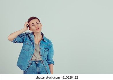 Amnesia. Closeup young woman short hair scratching head, thinking daydreaming something looking up isolated green grey wall background. Human facial expression emotion feeling body language perception