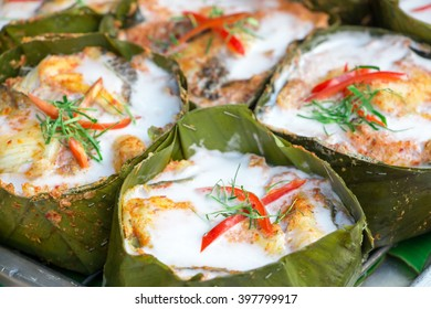 Amok or colorful and tasty steamed seafood in curry coconut paste wrapped with banana leaf on a stall of a grocery shop in Thailand