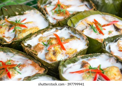 Amok or colorful and tasty steamed seafood in curry coconut paste wrapped with banana leaf at a grocery shop in Thailand