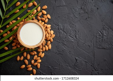 Amond seeds with bowl of fresh natural milk placed on black stone background. Palm leaf as a decoration. Top view. Copy space for text.
