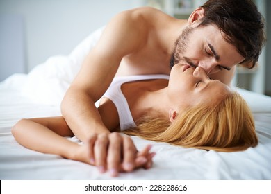 Amorous couple cuddling in bed