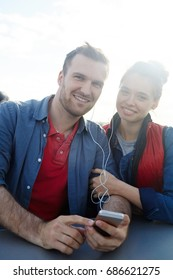 Amorous couple listening to music while traveling