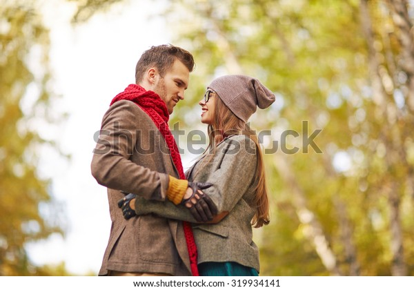 Amorous guy and girl looking at one another during date in park