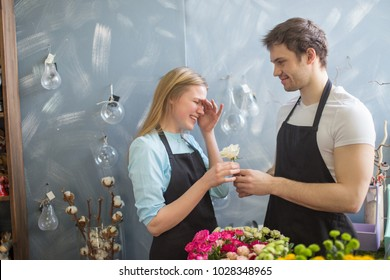 amorous shop assistant giving flower to his embarrased collegue