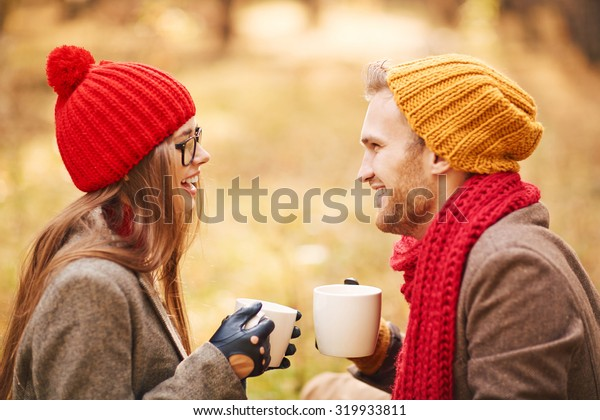 Amorous young couple with cups of tea talking outdoors