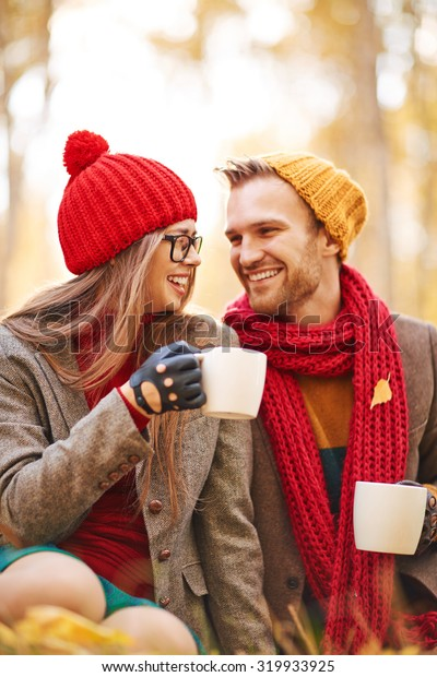 Amorous young couple talking and laughing while drinking tea in natural environment