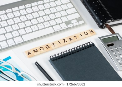 Amortization expense concept with letters. Still life of office workplace with supplies. Flat lay white surface with computer keyboard and calculator. Financial management, accounting and calculation