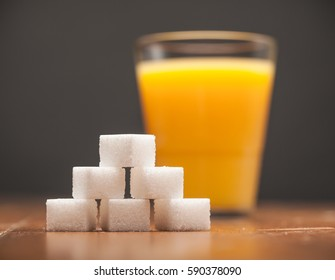 Amounts of Sugar In Food - Glass of Orange Juice, On wooden table and dark Background, Selective Focus