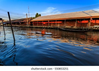 Ampawa Floating Market - December 18, 2016: Image monks alms boating morning for communities along the canal from Thailand to promote tourism.The house is on a wooden bridge.