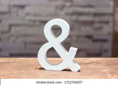 ampersand & sign on wood table with blurred wall background