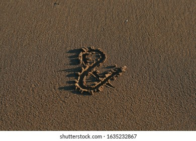 Ampersand symbol drawn on the sand