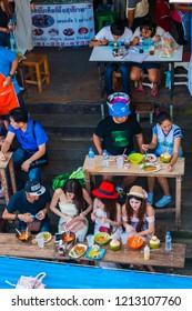 Amphawa, Thailand - Sep 13, 2015: Locals eating on the stairs at the river bank at Amphawa floating food market