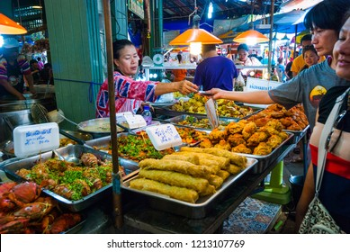 Amphawa, Thailand - Sep 13, 2015: Woman serving ready made food in Amphawa floating food market