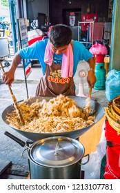 Amphawa, Thailand - Sept 13, 2015: Chef cooking rice on big gas stove at Amphawa food market in Thailand