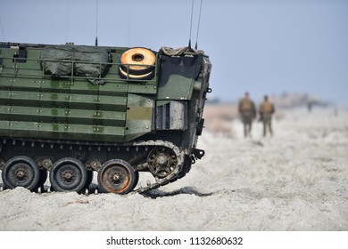 Amphibious tank caterpillars are seen on a beach in the sand