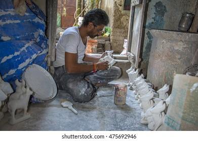 AMRAVATI, MAHARASHTRA - 26 AUGUST 2016 : Artist gives finishing touches on statue of Bull at an artist's workshop for Bail (Bull) Pola Festival, 26 August 2016, Maharashtra, India.