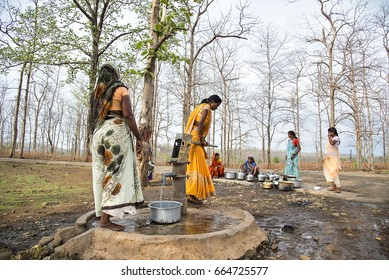 AMRAVATI, MAHARASHTRA, INDIA, 11 JUNE 2017 : Unidentified rural Indian women carry water on their heads in traditional pots from hand pump, everyday Women walk few kilometers to get it due to drought.