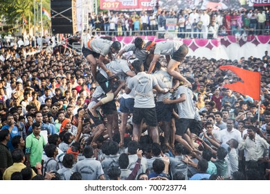 "AMRAVATI, MAHARASHTRA, INDIA - 15 AUGUST 2017 : Crowd of young People ""Govinda"" building human tower and enjoying the Dahi Handi festival to celebrate God Krishna's Birth, in Maharashtra, India."
