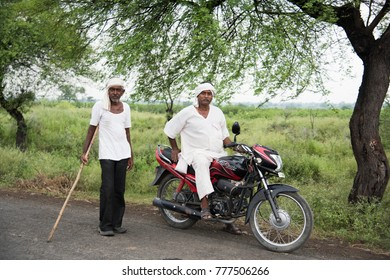 AMRAVATI, MAHARASHTRA, INDIA 22 NOVEMBER 2017 : unidentified Indian farmers came from their field on motorbike at village. Rural people daily lifestyle of India.