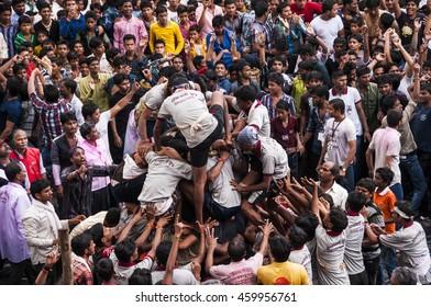 """AMRAVATI, MAHARASHTRA, INDIA - 29 AUGUST 2013 : Crowd of young People """"Govinda"""" enjoying the Dahi Handi festival to celebrate God Krishna's Birth in Amravati, Maharashtra, India."""
