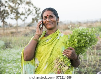 AMRAVATI, MAHARASHTRA, INDIA, 7 FEBRUARY 2017 : unidentified Indian woman holding bunch of green coriander in her hands and talking on phone at the organic farm.