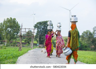 AMRAVATI, MAHARASHTRA, INDIA, 7 JULY 2015 : Unidentified rural Indian women carry water on their heads in traditional pots from well, everyday Women walk few kilometers to get it due to drought.