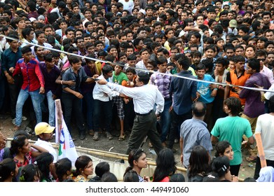 "AMRAVATI, MAHARASHTRA, INDIA - AUGUST 24 : Crowd of young People enjoying ""Govinda"" at Dahi Handi festival to celebrate God Krishna's Birth in Amravati, Maharashtra, India. 24 August 2014"