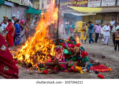 AMRAVATI, MAHARASHTRA, INDIA, MARCH - 1, 2018: unidentified people celebrating Holika Dahan by worshiping of wood logs or coconut. also known as the festival of colours Holi or the festival of sharing