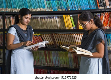 AMRAVATI, MAHARASHTRA,INDIA - 11 APRIL 2016 : Unidentified group of young students doing their studies together and leaning in front of bookshelf holding book's  at their college library.