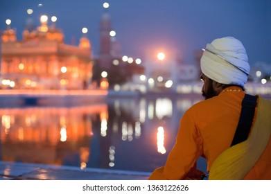 AMRITSAR, INDIA - AUG 25, 2011: Sikh warrior in traditional clothes looking at evening Golden Temple. Holy Sikh Place Harmandir Sahib (gurdwara Golden Temple). Amritsar, Punjab, India