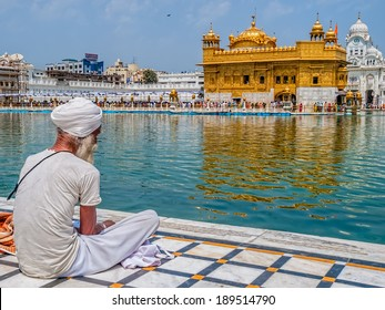 AMRITSAR, INDIA - MARCH 30, 2010: Sikh devotee sitting by the pool in front of the Golden Temple while Tourists and pilgrims entering  and walk towards The Harmandir Sahib (Golden Temple).