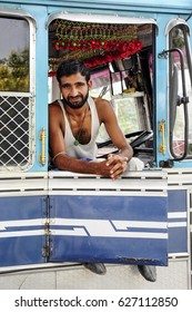Amritsar, India, september 5, 2010: Young indian man, truck driver, sitting and smiling in his truck. India.