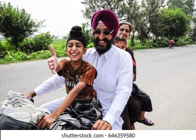 Amritsar, India, september 5, 2010: Sikh Indian family on a motorcycle with son pulling out his hand.