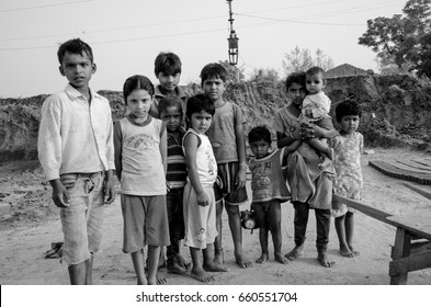 AMRITSAR, PUNJAB, INDIA - 21 APRIL 2017 : monochrome picture of indian kids holding their younger siblings