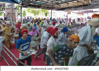 Amritsar Punjab India April 8th, 2014 Golden Temple Harmandir Sahib  Pilgrims collect  clean utensils from the stands and proceed towards the dining Hall for free food.