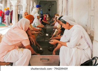 Amritsar, Punjab, India, May 07,2012: Women giving free service for serving to the mankind at Golden Temple or Sri Harmandir Sahib Gurdwara, Amritsar