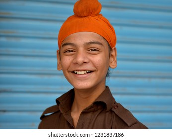 AMRITSAR, PUNJAB / INDIA - OCT 25, 2018: Indian Sikh teen boy wears an orange patka (Sikh head cover for boys) and smiles for the camera, on Oct 25, 2018.