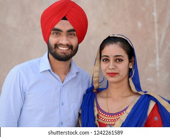 AMRITSAR, PUNJAB / INDIA - OCT 25, 2018: Fashion-conscious young Indian Sikh couple wears matching outfits in red and blue and looks into the camera, on Oct 25, 2018.