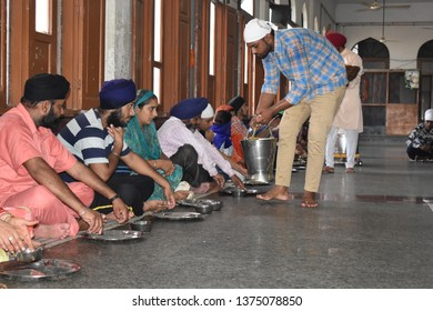 Amritsar, Punjab/India - August 16, 2018: Without discriminating against race and color, people are sitting down together eating food called langar in local language in golden temple amritsar, punjab