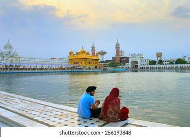 AMRITSAR/INDIA, JUNE 7: Young pair sit near the sacred lake in Golden Temple (Harmandir or Darbar Sahib) on June 7, 2014 in Amritsar, Punjab, Northern India. Golden Temple is the holiest Sikh gurdwara