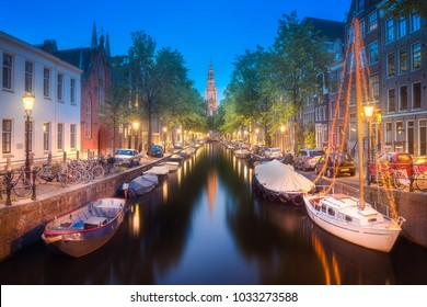 Amstel river, canals and boats against night cityscape of Amsterdam, Holland Netherlands