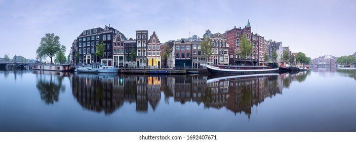 Amstel river, canals and boats against cityscape of Amsterdam, Holland Netherlands
