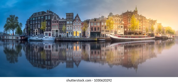 Amstel river, canals and sunrise over beautiful Amsterdam city. Netherlands.