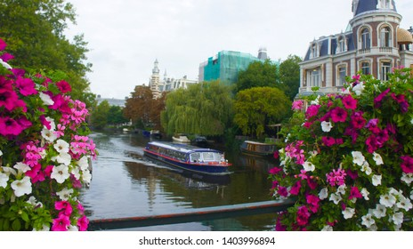 Amstel river, with sailing tourist boat and the background building in the Dutch style. Pink and white flowers in the foreground.C