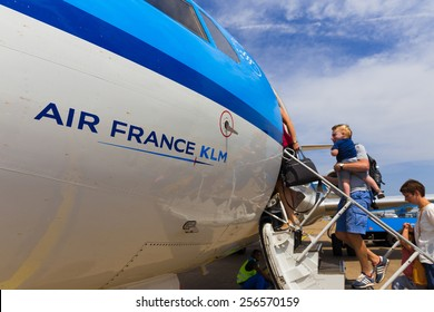 AMSTERDAM - 19 JULY, 2014: Travellers to Toulouse in France are boarding an Air France KLM Cityhopper Fokker F70 at Schiphol Airport in the Netherlands.