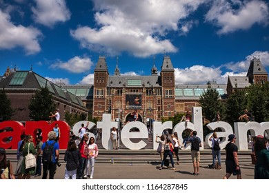 AMSTERDAM - 25 JUNE: tourists in the city center of Amsterdam, The Netherlands on 25 June 2018. Amsterdam is the capital of the Netherlands and receives around 25 million tourists yearly.