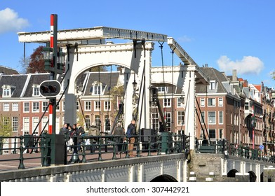 """AMSTERDAM - APR 30: The The Magere Brug (""""Skinny Bridge"""") and tourists in Amsterdam on April 30. 2015 in Netherlands. Skinny Bridge is a bridge over the river Amstel in the city centre of Amsterdam."""