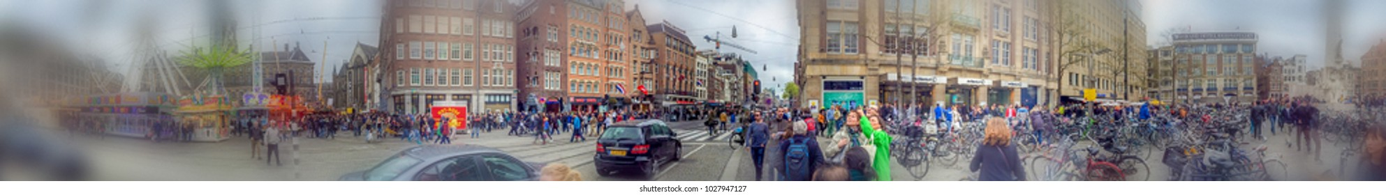 AMSTERDAM - APRIL 2015: Tourists walk in Dam Square. The city attracts 15 million people annually.